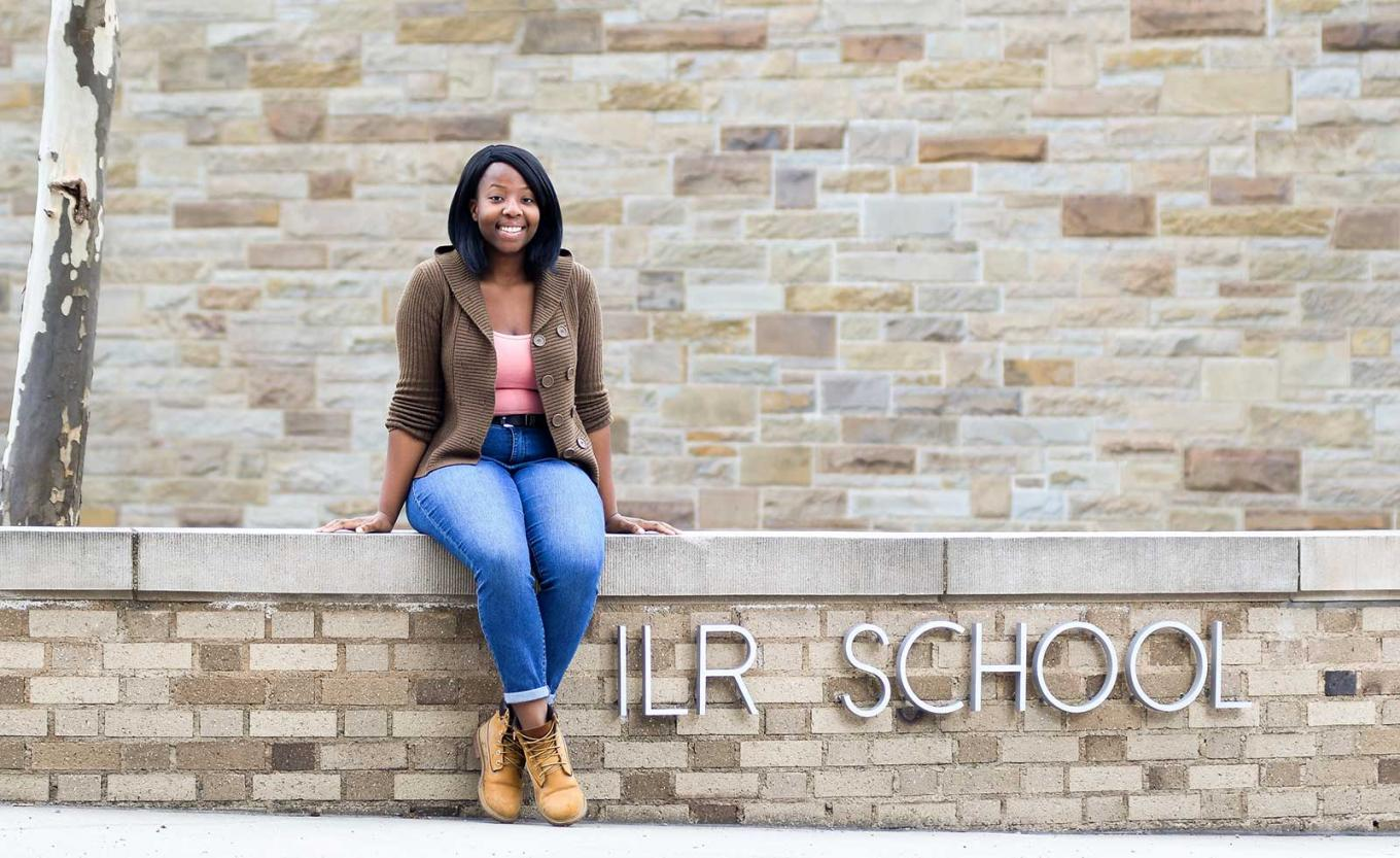 Grace Traore sits on wall of the ILR School