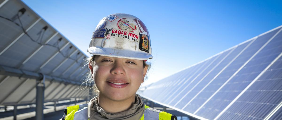 Union woman worker wearing a hard hat and standing in front of solar panels