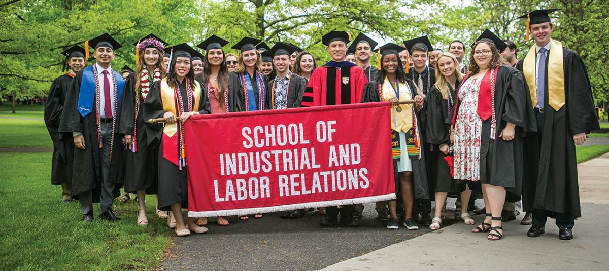 ILR graduates pose behind the school's banner that is carried during commencement
