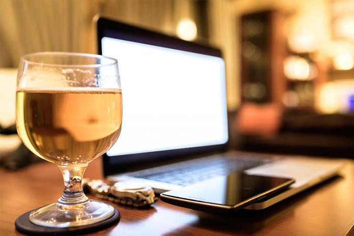 Beer glass next to wristwatch, smart phone and laptop
