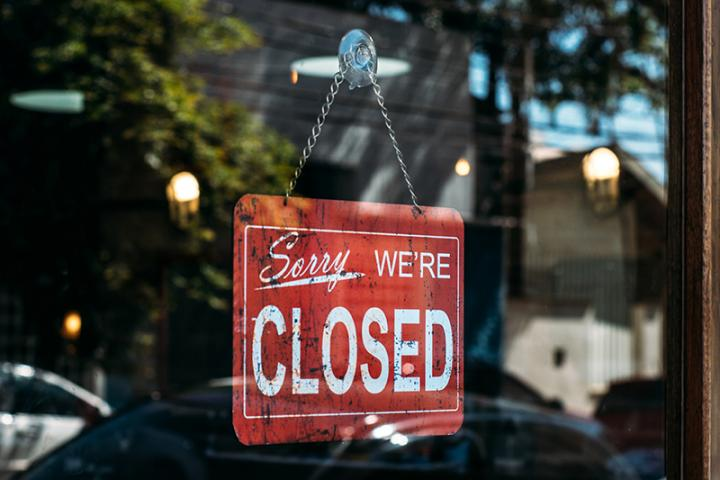"""Sorry, we're closed"" sign hanging on a business door."