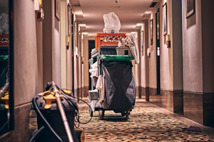 Housekeeping cart with cleaning supplies in a hotel hallway.