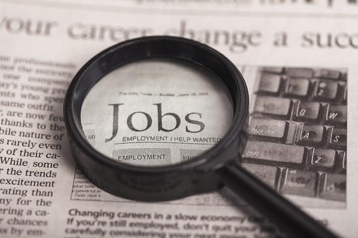A magnifying glass is held over the word jobs in a newspaper.