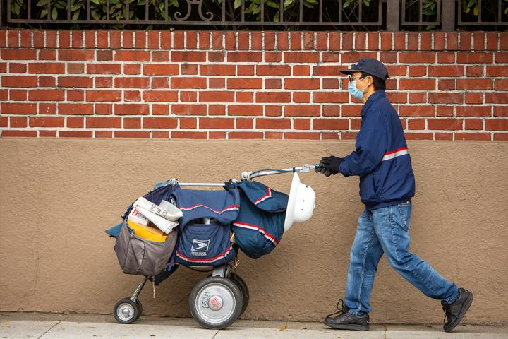 postal worker pushing a cart with mail