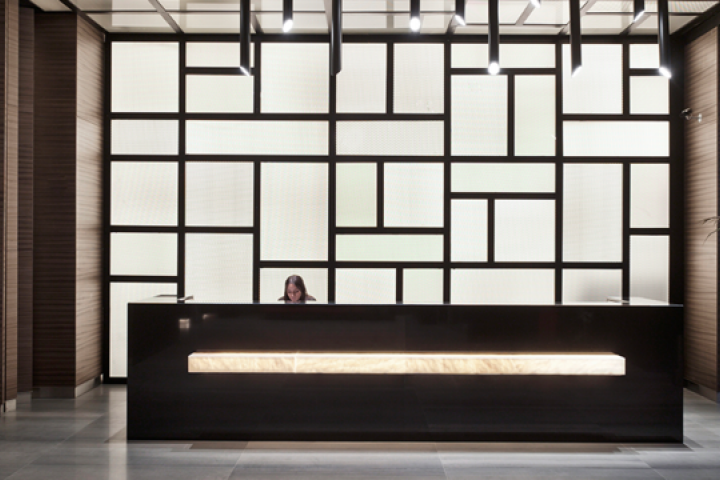 A woman sits behind a hotel reception desk