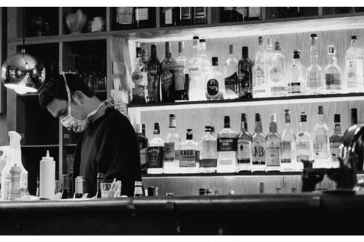 person wearing a mask working behind a bar at a restaurant