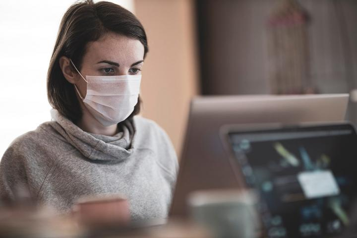 someone wearing a mask while working at a computer monitor