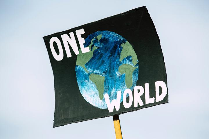"sign on a post saying: ""one world"" over a graphic of the globe to illustrate unity and the planet"