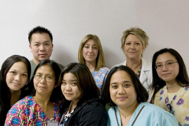 Eight healthcare workers pose for a group portrait