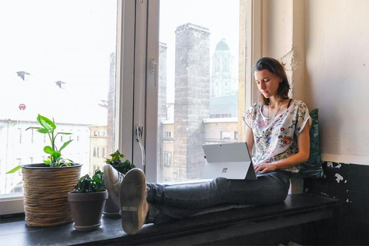 Young woman working on a laptop, sitting on a window sill.