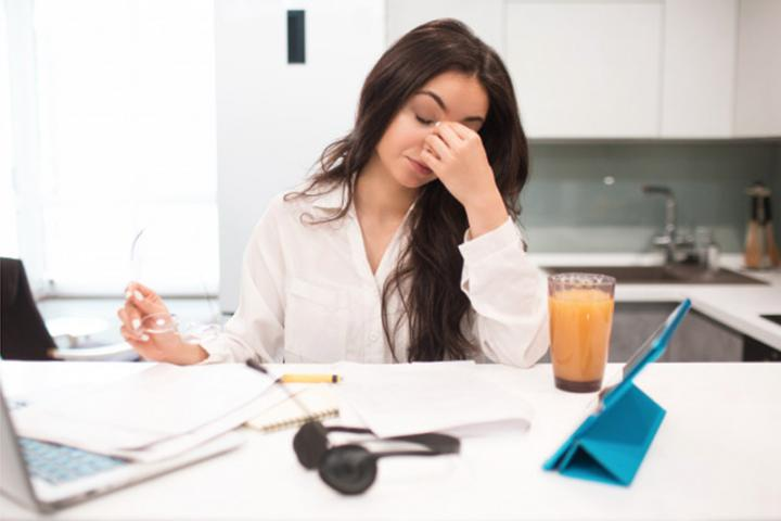 Frustrated young woman working at home. She is holding her glasses and is leaning her head on her hand.