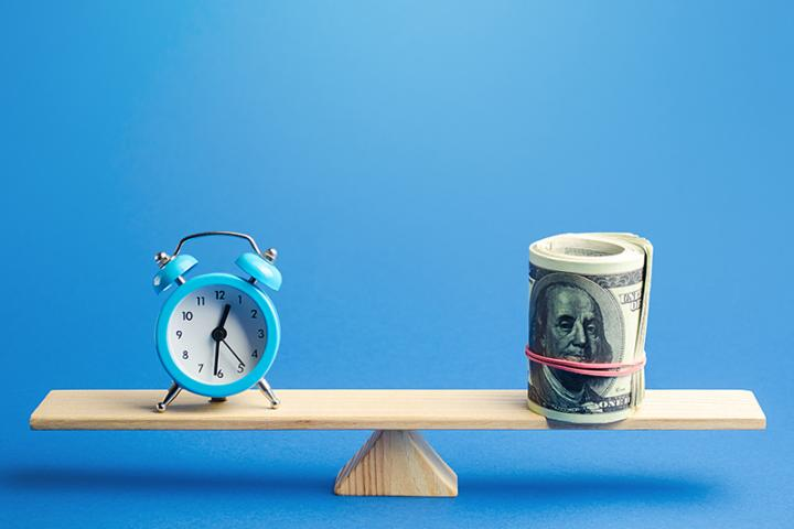 A clock and a roll of hundred dollar bills sit at opposite ends of a scale.