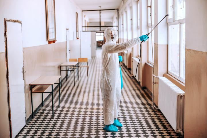 worker-sterile-white-uniform-with-mask-glasses-holding-sprayer-with-disinfectant-spraying-around-hallway-school-prevention-spreading-corona-virus