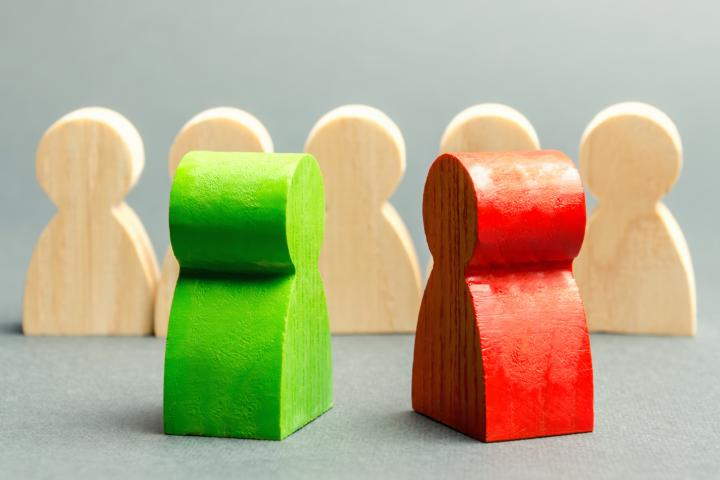 Red and green wooden figures on opposite sides of a divide