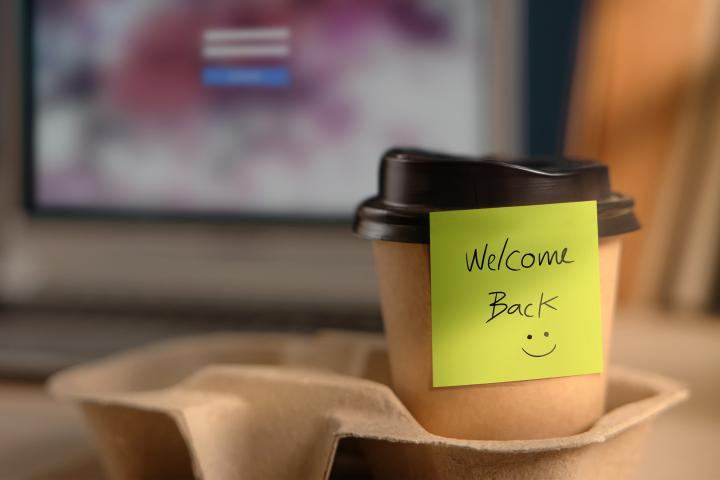 "A post-it note that says ""Welcome Back"" sticks to a take out coffee cup in front of a computer."