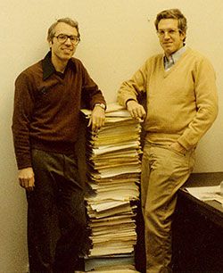 Bob Smith and Ron Ehrenberg stand on either side of a chest-high stack of papers