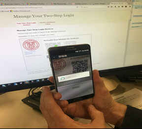 Someone holding their iPhone to a computer screen to read the verification barcode to enroll the device as a two-step authentication device.