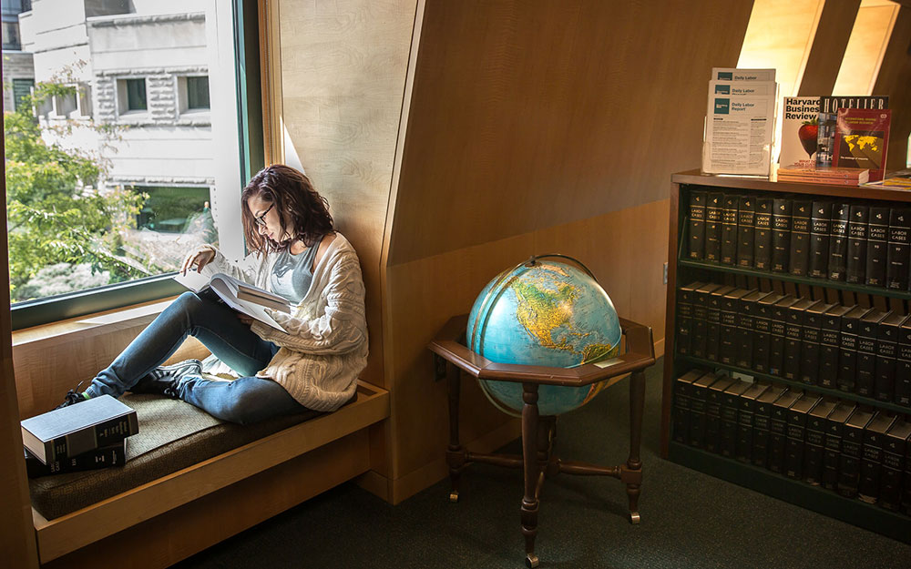 Student sits reading in a window of Catherwood's main reading room with a globe and a shelf of books to her right