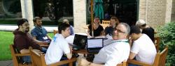 participants working outside at a round table under a café umbrella