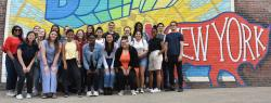 Students stand in front of painted wall mural in Buffalo, NY. The word Buffalo rises out of a bright sun and the words New York are inside a buffalo (bison).