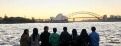 Students in the University of New South Wales exchange program sit at the edge of Sydney Harbor looking out at the Opera House