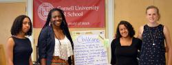 Four ILR students stand in front of a poster labeled Childcare