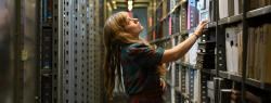 Marcie Farwell looking at a shelf in the library stacks