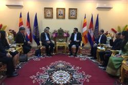 Several dignitaries sit in conference with the Cambodian minister of labor, seated at center.