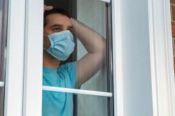 Man in a medical mask near the window.