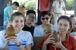 Students drinking coconut milk from the shell on the trip to Mekong.
