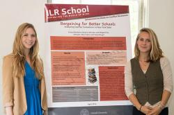 Two undergraduate researchers stand on either side of their poster for Bargaining for Better Schools