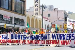 Protestors hold a banner that spans the full width of a city street reading, Full rights for immigrant workers. Comprehensive immigration reform now.