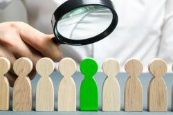 Wood figures in a row with a single green one being singled out by a businessman with a magnifying glass.