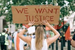 """A young woman at a protest holds a sign that reads """"We Want Justice"""""""