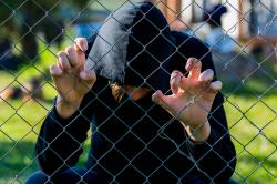Teenage boy holding wired fence at correctional institute.