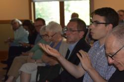 A young man seated among a room full of event participants speaks to the facilitator while gesturing with his hands.