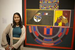 Camilla Bacolod stands next to a painting referencing games of chance and hand guns