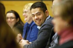 A young man seated with other event participants turned toward camera, smiling.