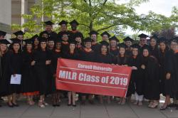 The gratuating MILR class of 2019 stand for a group shot in front of a tree in their graduation gowns holding a class banner.