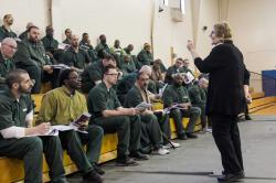 Esta Bigler speaks to inmates seated on bleachers at Cayuga Correctional facility