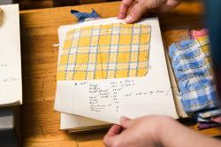 older fabric swatch saved in a book with handwritten notations