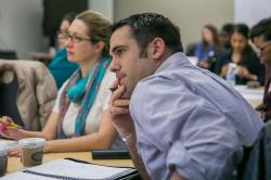 A young man with hand to chin leaning forward in attention in a room full of other event participants