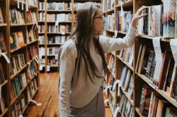 A young woman browses shelved books in a book swtore