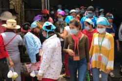 Photograph of Garment workers in Cambodia exiting factory.