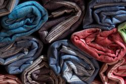 Photograph of rolled up garments of different colors.