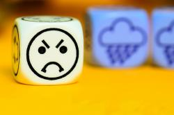 A six-sided die shows an angry emoji with two dice in the background showing rain clouds