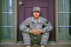 army military member in uniform sitting on doorstep of home