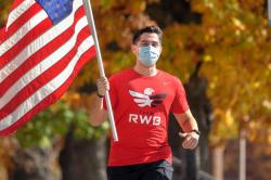 Michael Sanchez, a veteran of the United States Marines and ILR student, carries an American flag while on a weekly run with Team Red, White and Blue, a nonprofit veterans organization.