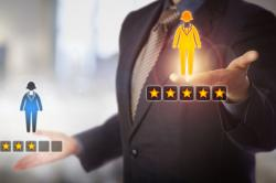 Unrecognizable manager is evaluating a female employee icon with a five star rating versus one with three.