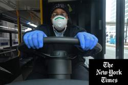 A bus driver in Detroit wearing protective gear to help prevent the spread of the coronavirus.Credit...Seth Herald/Agence France-Presse — Getty Images